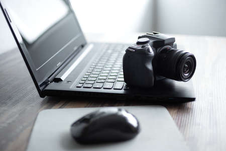 Photographer or stock photography concept, digital black camera near laptop on desk workstation
