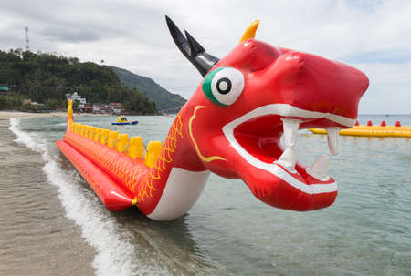 Inflatable red dragon float boat in White beach, Puerto Galera, Philippines