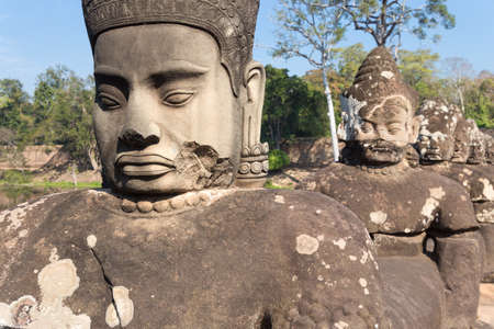 Stone statues on the bridge near southern gates to Bayon temple, Angkor Wat complex, Cambodia Фото со стока