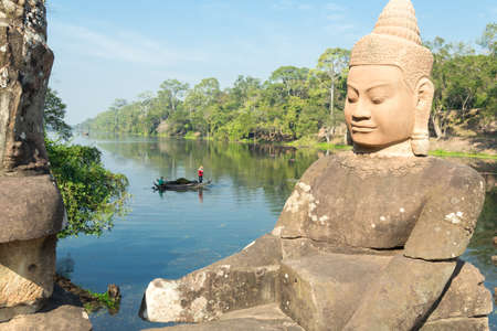 Stone statues on bridge near lake or river and southern gates to Bayon temple, Angkor Wat complex, Cambodia Фото со стока