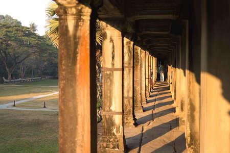 Long corridor of pillars in temple ruins, Angkor Wat, Cambodia Фото со стока