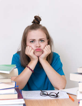 Young caucasian girl woman with many books study at school or university, looks tired, stressed or exhausted