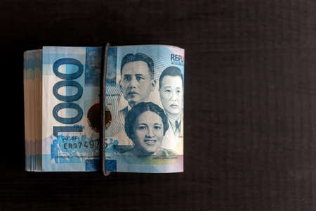 Folded bundle of money in cash of one thousand Philippines peso. Bribe, investment, paying bills or getting salary (black background)