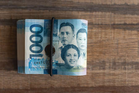 Folded bundle of money in cash of one thousand Philippines peso. Bribe, investment, paying bills or getting salary. Archivio Fotografico