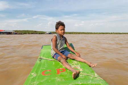 Siem Reap, Cambodia - January 31, 2017: Cambbodian poor boy sitting on old tourist boat in the river