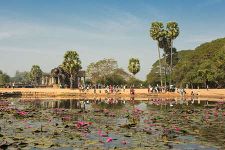 Landscape of Angkor Wat temple complex, pond with lotuses, trees and gates to temple, Siem Reap, Cambodia