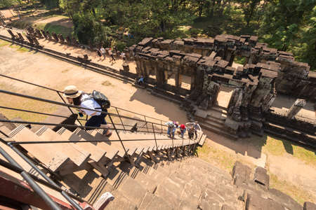 Cambodia, Angkor Wat, Siem Reap - January 30, 2017: Tourists climb the stairs to the pyramid temple, view from above