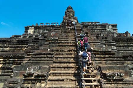 Cambodia, Angkor Wat, Siem Reap - January 30, 2017: Tourists climb the stairs to the pyramid temple, bottom view Редакционное