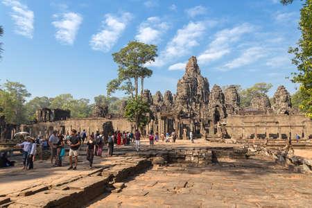 Siem Reap, Cambodia - January 30, 2017: Group of tourists walking around Angkor Wat temple complex Редакционное