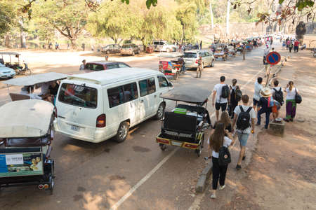 Siem Reap, Cambodia - January 30, 2017: Group of many tourists, tuktuks and cars walking around Angkor Wat temple complex