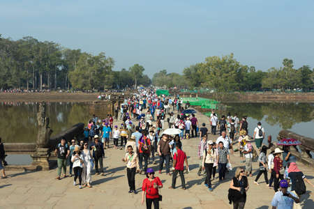 Siem Reap, Cambodia - January 30, 2017: Group of tourists walking around crowded Angkor Wat temple complex