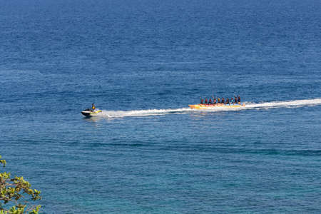 Puerto Galera, Philippines - April 4, 2017: A man riding jet ski in the sea, people on banana boat near White beach