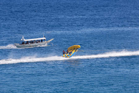 Puerto Galera, Philippines - April 4, 2017: A man riding jet ski in the sea, people on flying fish near White beach 스톡 콘텐츠