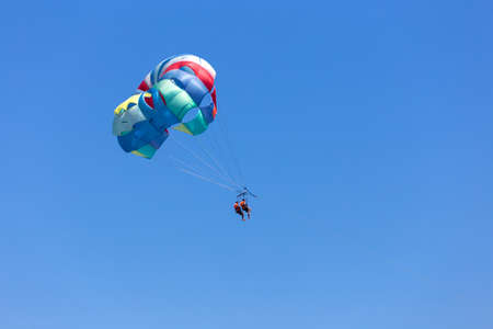 Two people parasailing in a blue sky