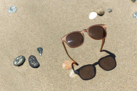 Sunglasses in the sandy beach. Hot summer concept 스톡 콘텐츠