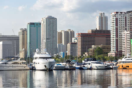 Manila, Philippines - May 16, 2017: Seascape of boats in Manila bay area, reflection of sea and big city 스톡 콘텐츠
