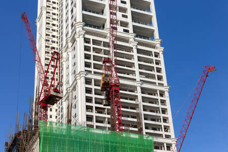 Manila, Philippines - May 16, 2017: Process of building, cranes at work on construction site 스톡 콘텐츠
