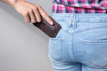 Pickpocketers hand pulling stealing wallet out of the back pocket, close up