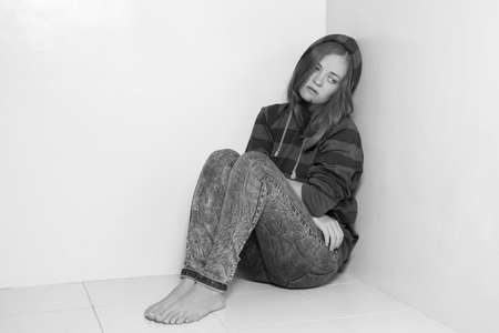 Young caucasian girl woman sitting on the floor, crying, upset, abused or depressed. Black and white