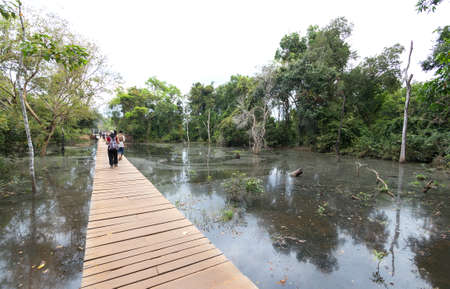 Siem Reap, Cambodia - February 2, 2017: Tourists people walking on bridge over the pond river in Angkor Wat temple
