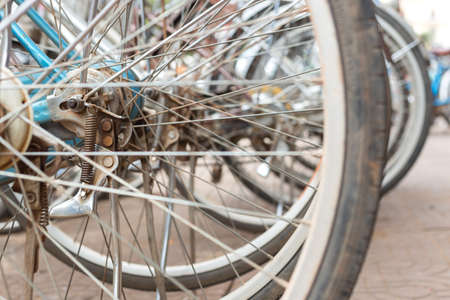 Bicycle wheels in a row parked in bike rack or rental shop, close up