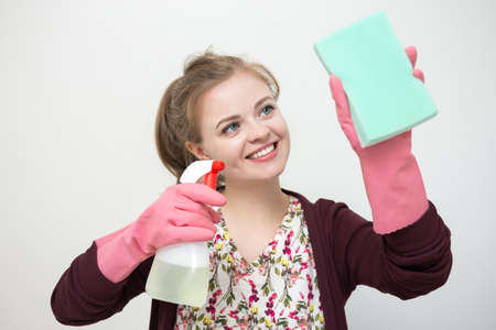 Smiling young caucasian girl woman with rubber gloves, sponge and sprayer, cleaning the house 스톡 콘텐츠