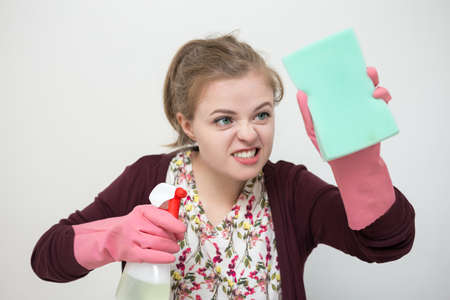 young caucasian girl woman with rubber gloves, sponge and sprayer, cleaning the house