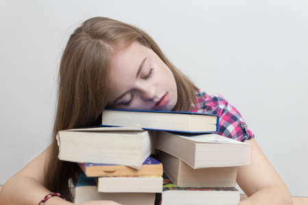 Young caucasian girl woman sleeping with many books at school or university, looks tired, stressed or exhausted 스톡 콘텐츠