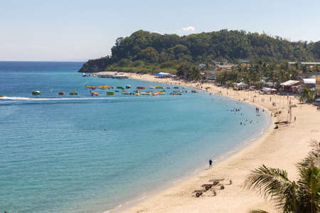 Puerto Galera, Philippines - April 4, 2017: Sea, blue sky, palms, tourists and boats in White beach, Sabang.