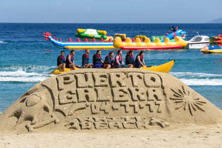 Puerto Galera - April 4, 2017: Sand castle with sign Puerto Galera on White beach with tourists and water activities on background 에디토리얼