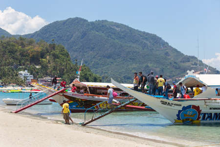 Puerto Galera, Sabang, Philippines - April 4, 2017: Passengers tourists on boats in  White beach.