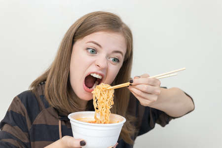 Young caucasian girl woman eating instant noodles ramen with chopsticks 写真素材
