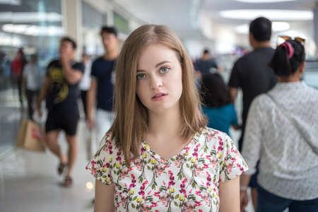Młoda kobieta kaukaski dziewczyna wyróżnia się z tłumu sama. Koncepcja samotności Zdjęcie Seryjne