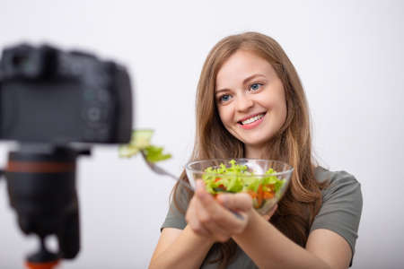 Young caucasian girl woman making a video blog (vlog) with camera about healthy vegetarian lifestyle