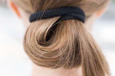 Close up of blonde fair casual hair bun in pony tail, macro