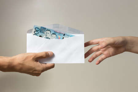 Hand holding giving cash banknote of one thousand Philippines in envelope peso paying bills, payment or bribe, salary
