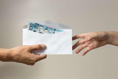 Mano che tiene una banconota in contanti di mille Filippine in peso di busta pagando bollette, pagamento o tangente, stipendio Archivio Fotografico