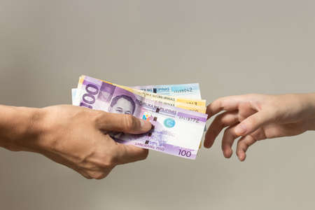 Hand holding giving cash banknotes Philippines peso paying bills, payment procedure or bribe, salary