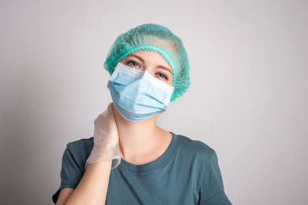 Young caucasian woman doctor nurse in surgical mask looks tired Banque d'images