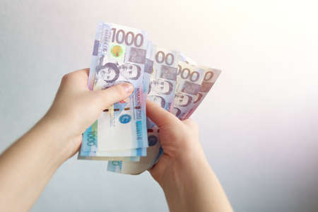 Hands holding cash banknote of one thousand Philippines peso paying bills, payment or salary. White background, close up
