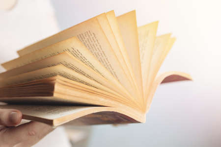 Vintage close up of an old open book with yellow pages. Avid reader, bookworm concept