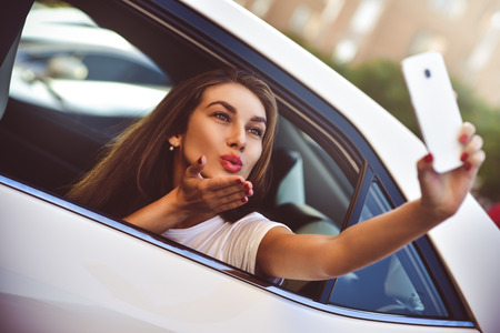 Young woman in the car going on holiday as a passenger makes selfie. Stockfoto