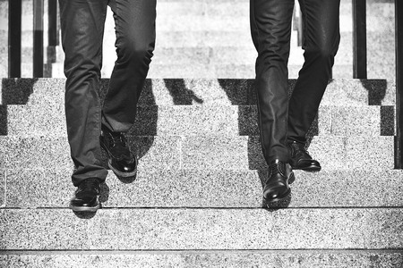 Two businessman stepping downstairs in a rush hour. Hurry time Stock Photo