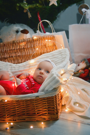A cute newborn baby in xmas clothes sleeping in a basket on the floor against a Christmas decoration. New Years Eve.