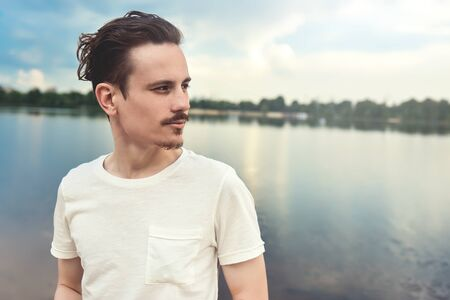 Portrait of Young Man Enjoys a beautiful view and looks into the distance near a lake and forest . summer . spring. nature 版權商用圖片