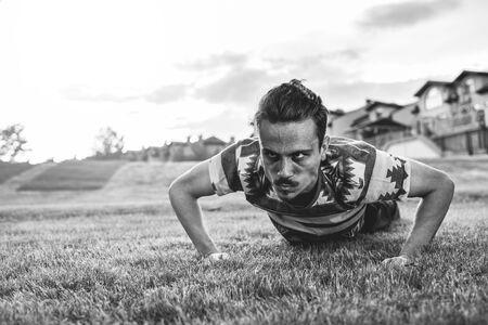 Deporte. Atleta haciendo flexiones al atardecer en el parque. chico flaco haciendo ejercicio y tratando de ponerse en forma.