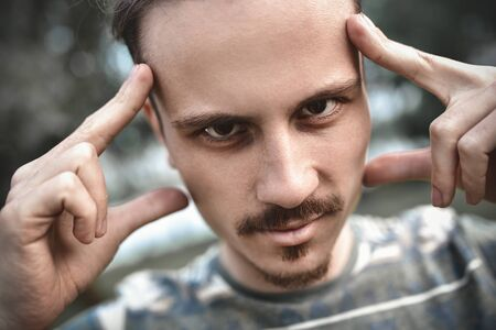 mind games and brain power. mentalist and cognitive skills concept. man concentrating and holding index fingers on temples. young bearded guy portrait Stock Photo