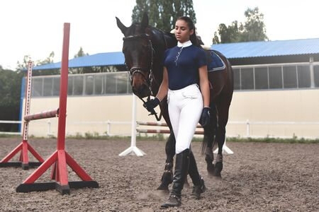 Young woman leads her horse to training and preparing it for the races