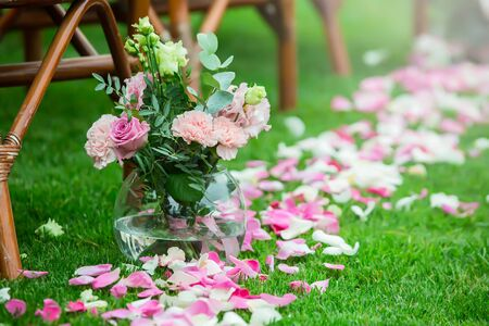 Outdoor wedding ceremony decoration setup. Path with petals, chairs decorated with colorful ribbons