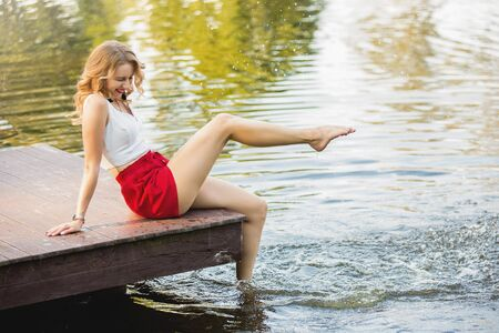 happy attractive young woman at a lake having fun and splashing water sitting on the pier in summer. good time. Banco de Imagens